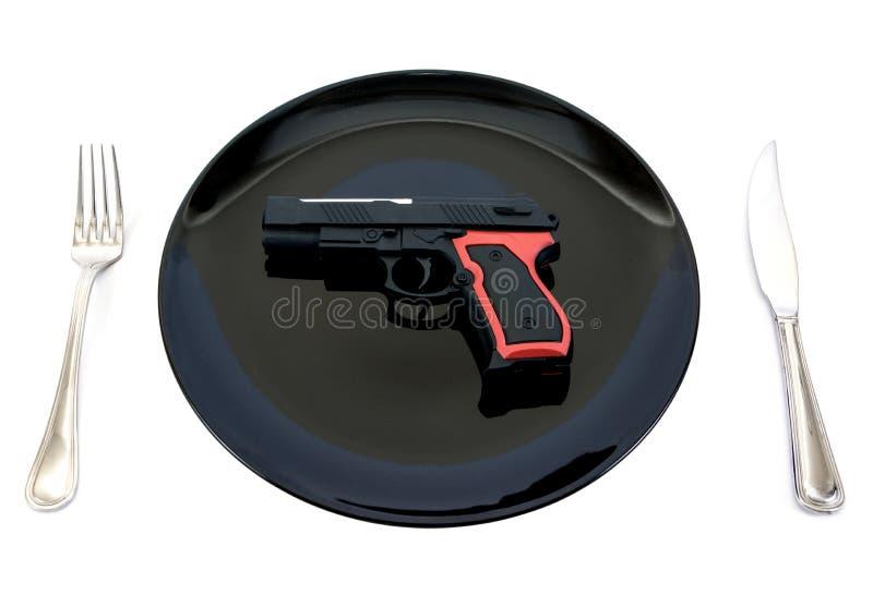 Brinquedo da arma da pistola na placa com forquilha e na faca isolada no fundo branco fotografia de stock royalty free