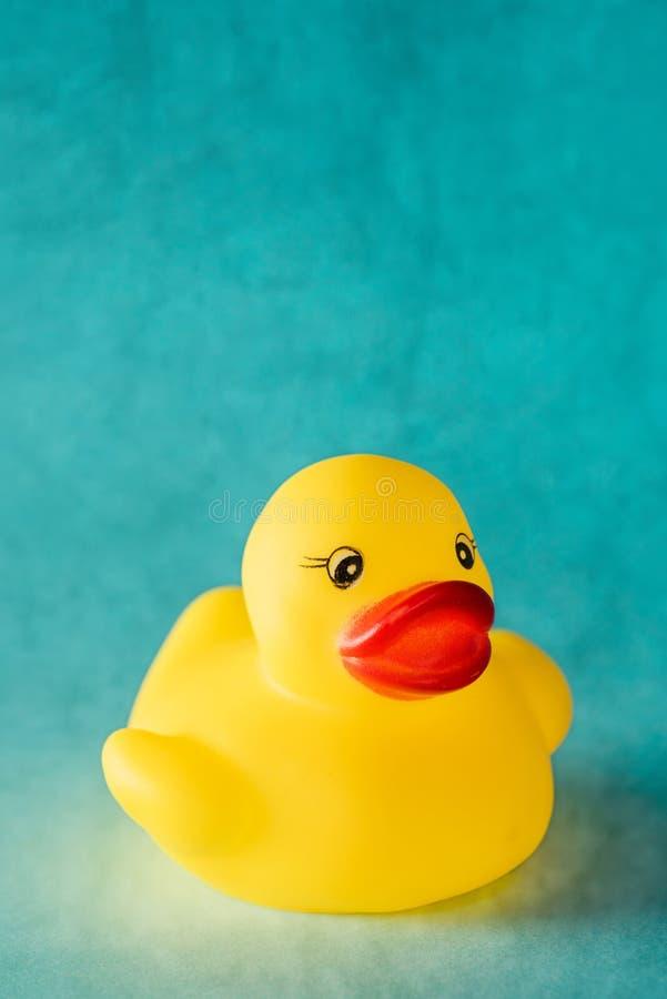 Brinquedo de borracha amarelo do pato no fundo azul imagem de stock royalty free
