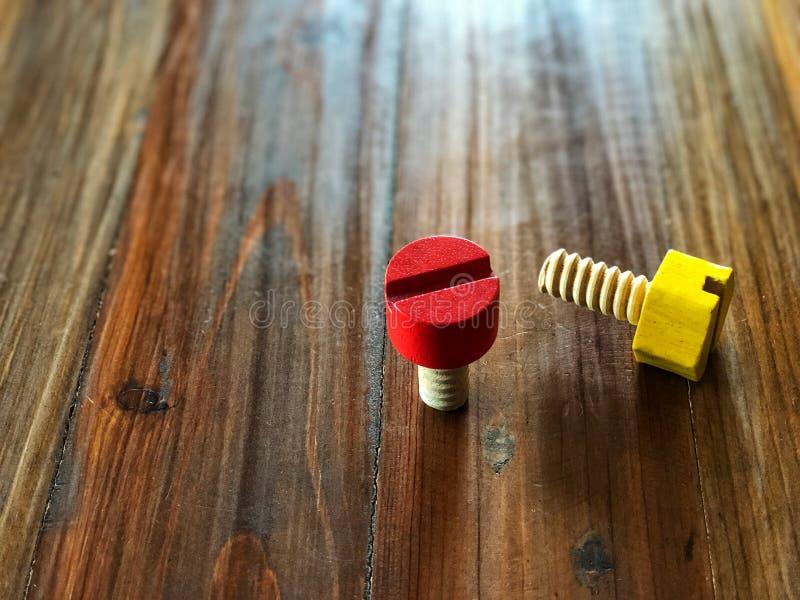 Brinquedo de madeira colorido Porcas vermelhas e amarelas na tabela de madeira do vintage imagem de stock royalty free