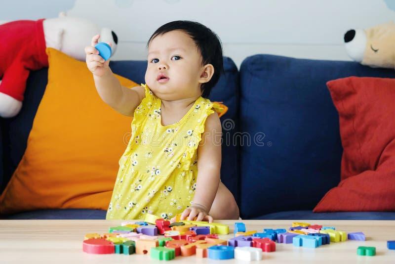 Brinquedo de madeira do enigma de serra de vaivém do jogo da menina do close up no sofá no fundo da sala de visitas fotos de stock royalty free