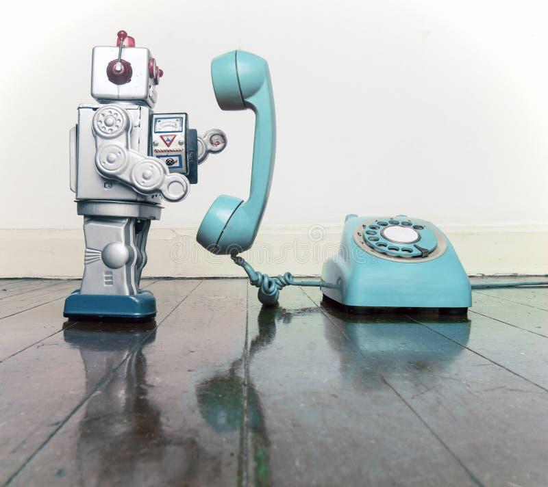 Brinquedo de prata grande do robô em uma posição azul do telefone imagem de stock