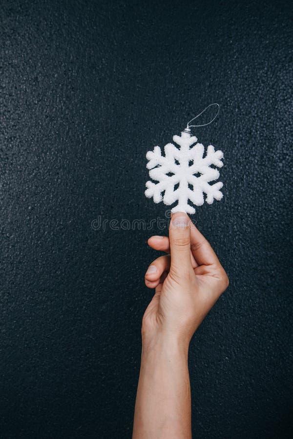 Brinquedo de suspensão do floco de neve da terra arrendada da mão da mulher para a decoração do Natal isolada no fundo preto Cart fotografia de stock royalty free