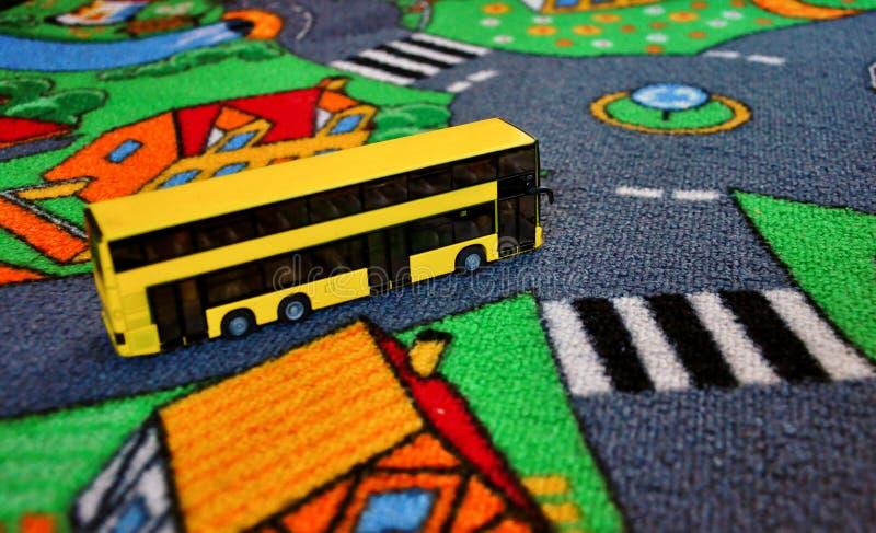Brinquedo do ônibus no tapete das crianças fotos de stock