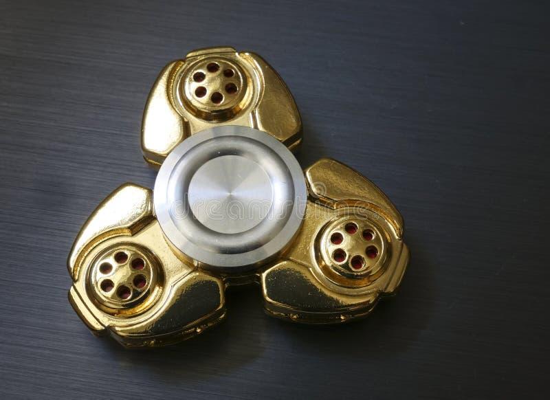 Brinquedo dourado do girador da inquietação no aurface escuro fotografia de stock