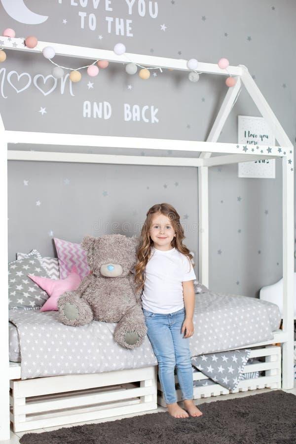 Brinquedo favorito A crian?a da menina senta-se no urso de peluche do abra?o da cama em seu quarto A crian?a prepara-se para ir p foto de stock royalty free