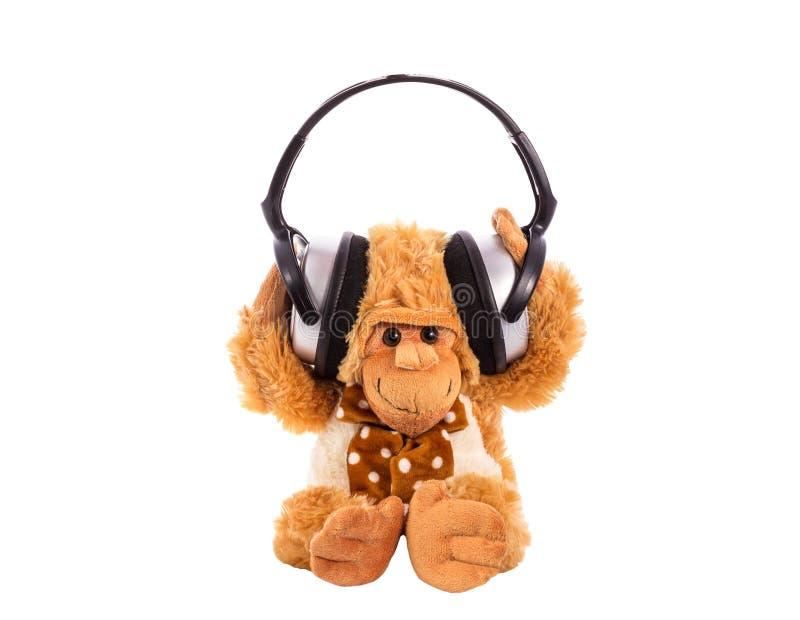 Brinquedo macio um macaco nos fones de ouvido fotografia de stock