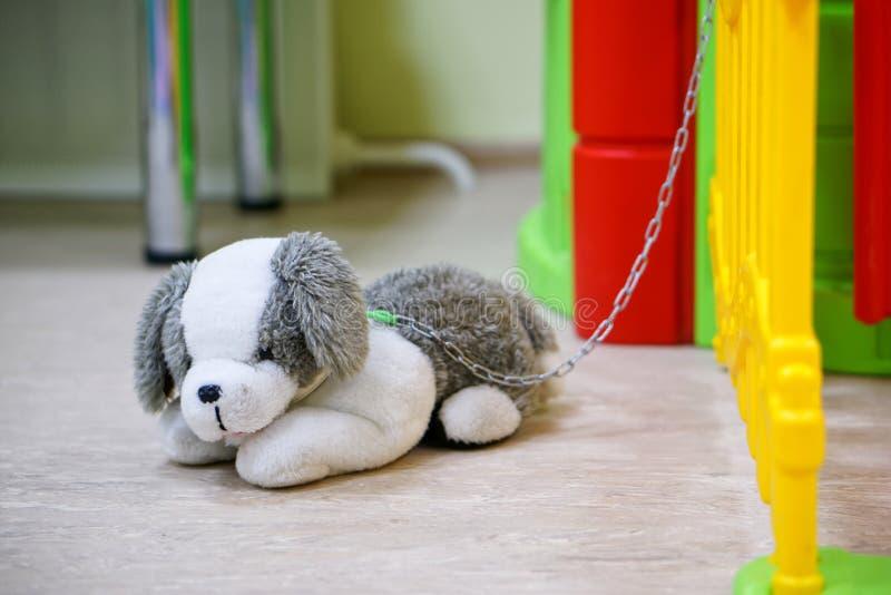 Brinquedo pequeno - um cão pincelado acorrentado com uma corrente de plástico até uma cerca de brinquedo Símbolo da tristeza e da fotos de stock