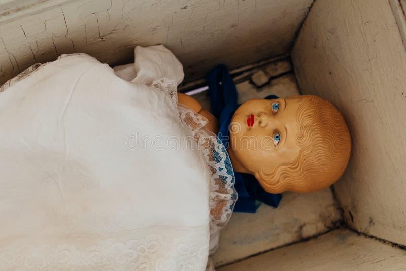 Brinquedo plástico da boneca do vintage velho na cama pequena do berço fotos de stock