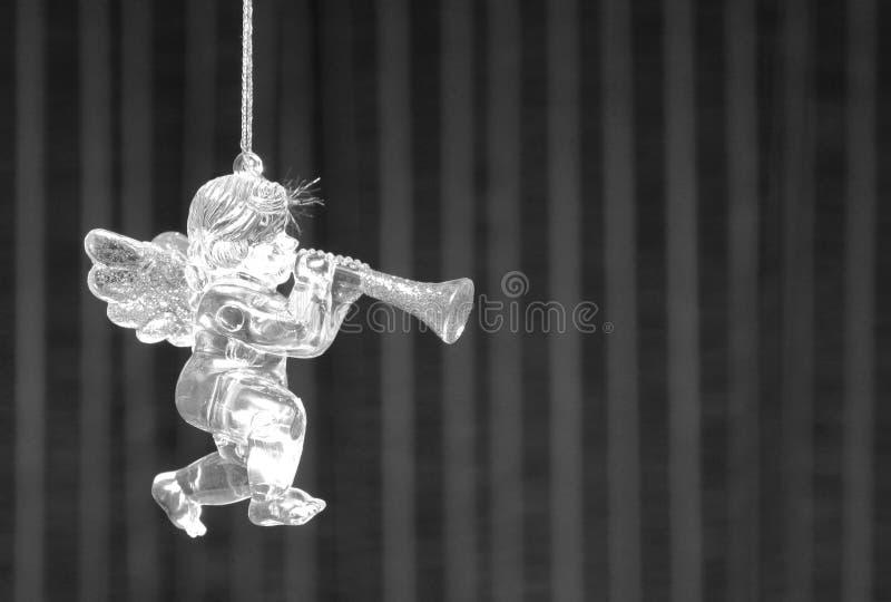 Brinquedo preto e branco da pele-árvore no formulário de pouca estatueta do ` s do anjo com asas e tubulação no fundo preto e bra imagem de stock