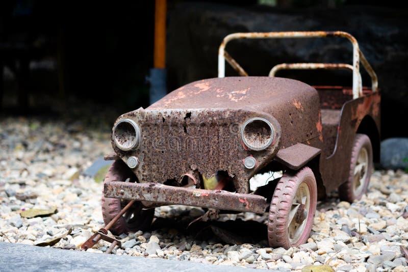 Brinquedo velho do carro do vintage com estacionamento de superfície oxidado no assoalho de pedra do cascalho imagens de stock