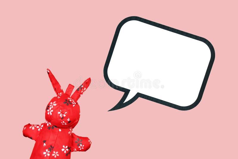 Brinquedo vermelho de pano do coelho com bolha vazia do discurso no fundo cor-de-rosa fotos de stock royalty free