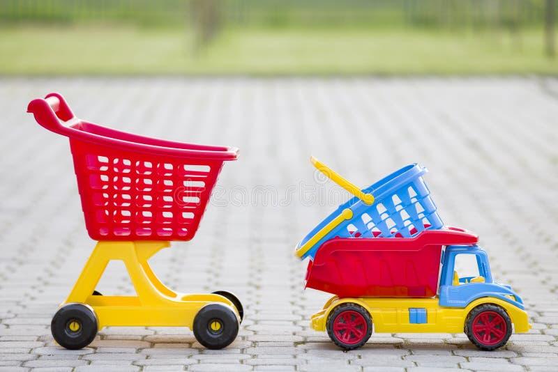 Brinquedos coloridos plásticos brilhantes para crianças fora no dia de verão ensolarado Caminhão do carro, cesta e carro de mão d foto de stock royalty free