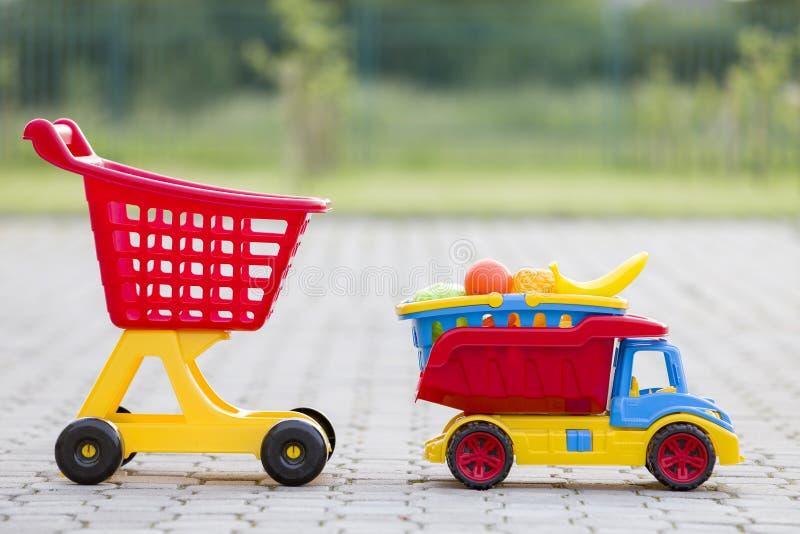 Brinquedos coloridos plásticos brilhantes para crianças fora no dia de verão ensolarado Cesta levando do caminhão do carro com fr fotos de stock