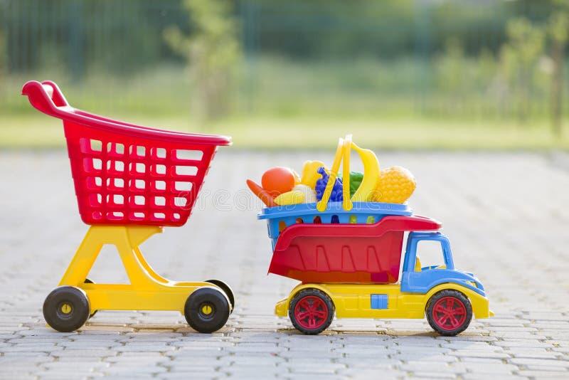 Brinquedos coloridos plásticos brilhantes para crianças fora no dia de verão ensolarado Cesta levando do caminhão do carro com fr foto de stock