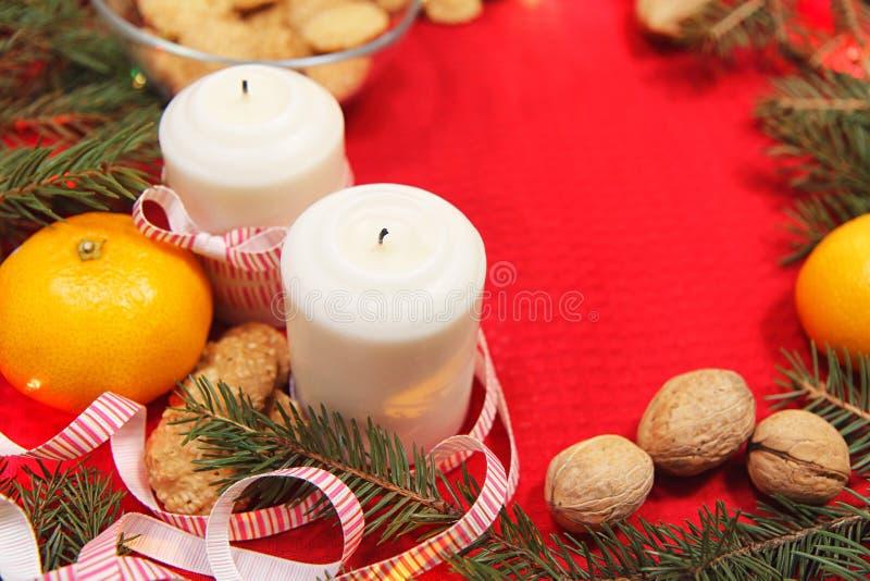 Brinquedos da árvore de Natal em um guardanapo vermelho Os mandarino e velas no th imagem de stock royalty free