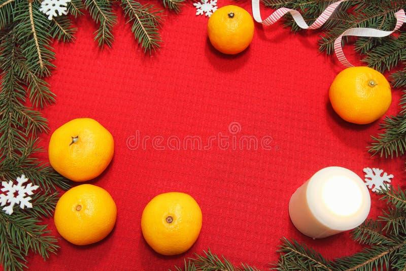 Brinquedos da árvore de Natal em um guardanapo vermelho Os mandarino e velas no th imagem de stock