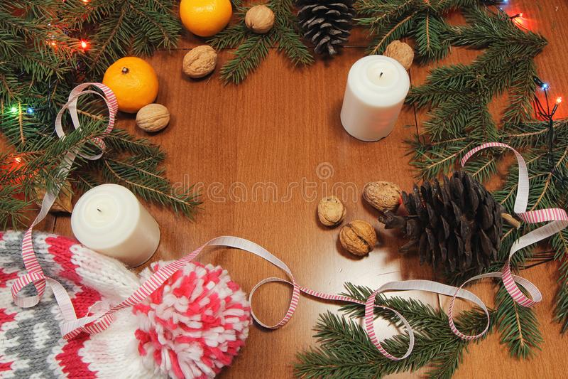 Brinquedos da árvore de Natal em um guardanapo vermelho Os mandarino e velas no th imagens de stock royalty free