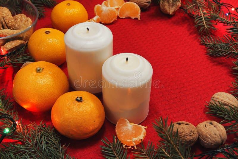 Brinquedos da árvore de Natal em um guardanapo vermelho Os mandarino e velas no th imagens de stock