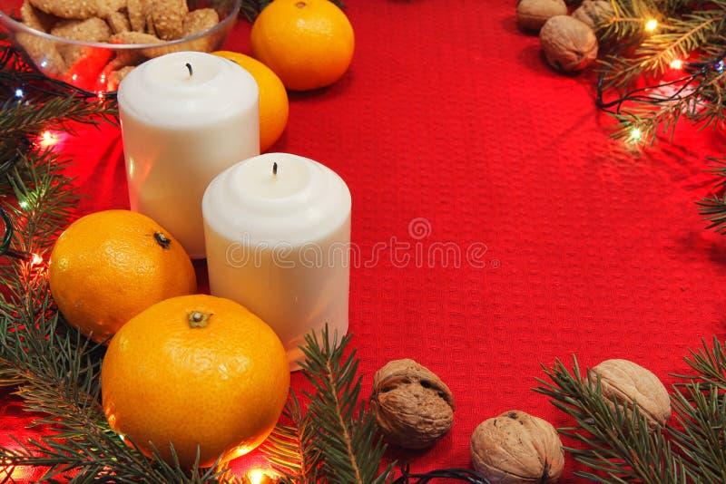 Brinquedos da árvore de Natal em um guardanapo vermelho Os mandarino e velas no th fotos de stock royalty free