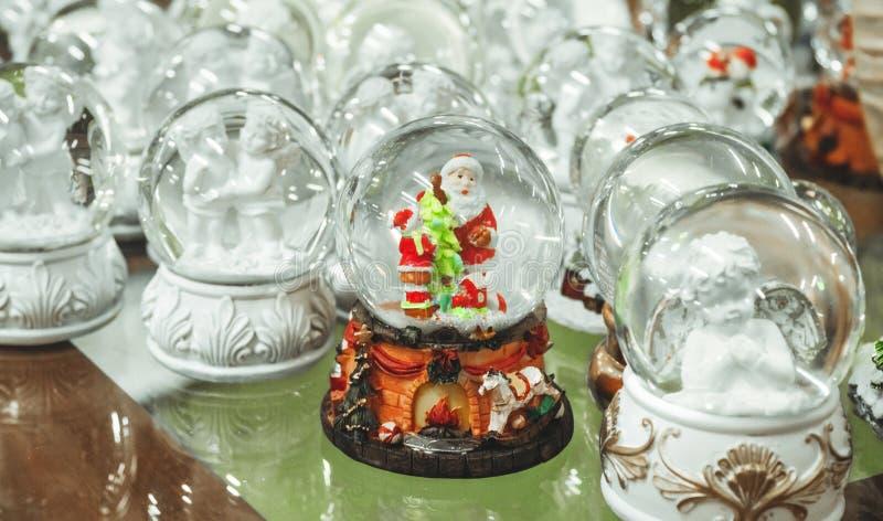 Brinquedos de vidro do Natal, lembranças - bolas de neve no contador do mercado do Natal imagens de stock