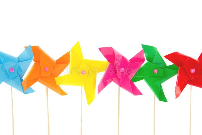 Brinquedos diminutos coloridos dos windmils de uma fileira foto de stock