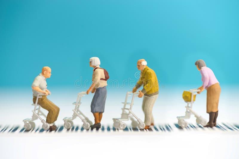 Brinquedos diminutos um o grupo de pessoas adultas com a cadeira de roda que cruza uma estrada - conceito da segurança rodoviária foto de stock royalty free