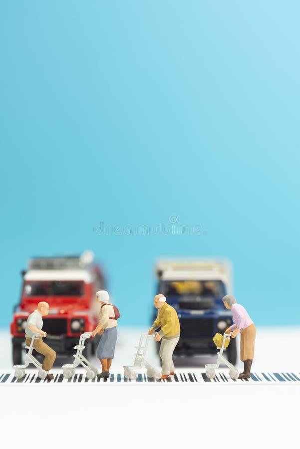 Brinquedos diminutos um o grupo de pessoas adultas com a cadeira de roda que cruza uma estrada - conceito da segurança rodoviária fotografia de stock