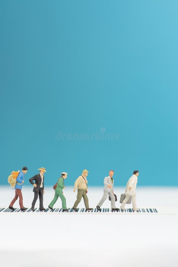 Brinquedos diminutos um o grupo de pessoas que cruza uma estrada - conceito da segurança rodoviária imagem de stock royalty free