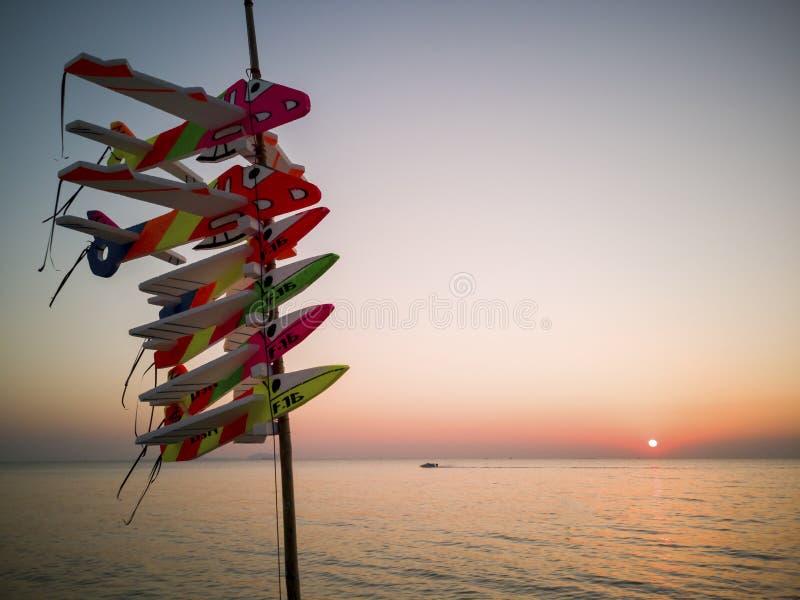 Brinquedos do avião com fundos do mar, barcos de banana, mar e fundos da areia no tempo do por do sol com céu crepuscular foto de stock royalty free