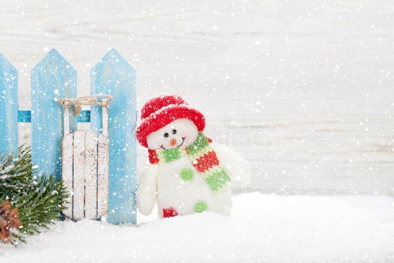 Brinquedos do boneco de neve e do pequeno trenó do Natal e ramo de árvore do abeto foto de stock royalty free