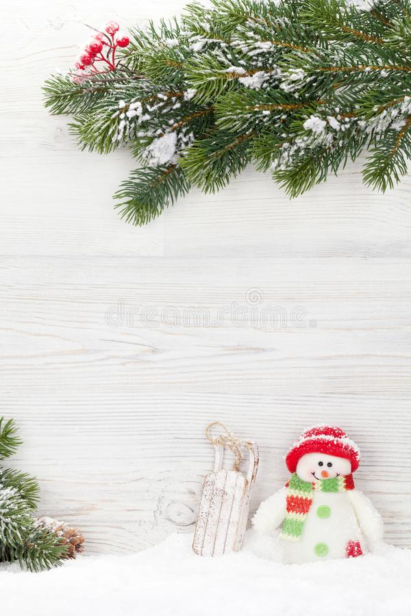 Brinquedos do boneco de neve e do pequeno trenó do Natal e ramo de árvore do abeto imagem de stock