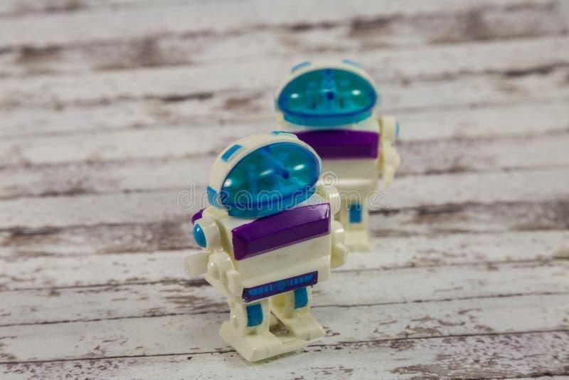 Brinquedos plásticos pequenos do robô na tabela de madeira branca fotos de stock royalty free