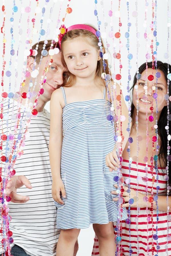 Brins de famille derrière des rideaux des programmes en plastique photos libres de droits