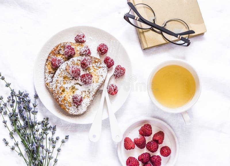 Brioche Franse toost met framboos, gepoederde suiker en groene thee Comfortabel huisstilleven, vrije tijdrust op een lichte achte royalty-vrije stock afbeelding