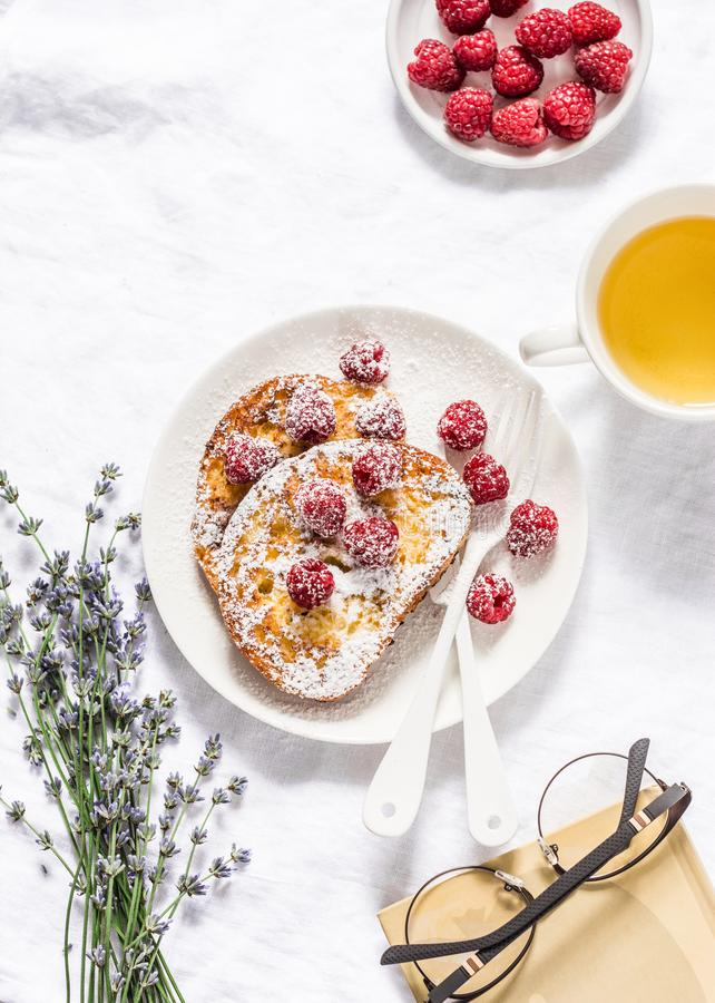 Brioche french toast with raspberry, powdered sugar and green tea. Cozy home still life, free time rest. On a light background, to stock photography