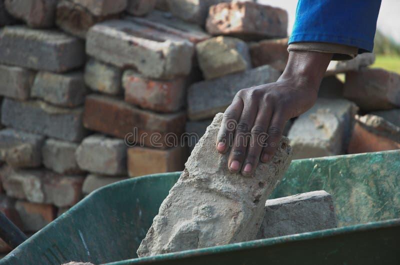 Briques, mains et brouette photos stock