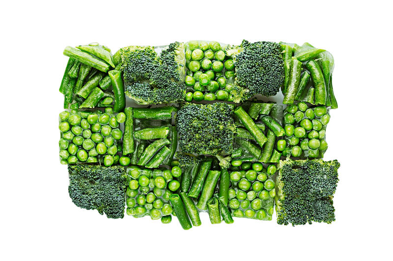 Briquette of assortment fresh frozen green peas, french bean, broccoli with hoarfrost closeup on white background. Isolated. Healthy vitamin food stock photo