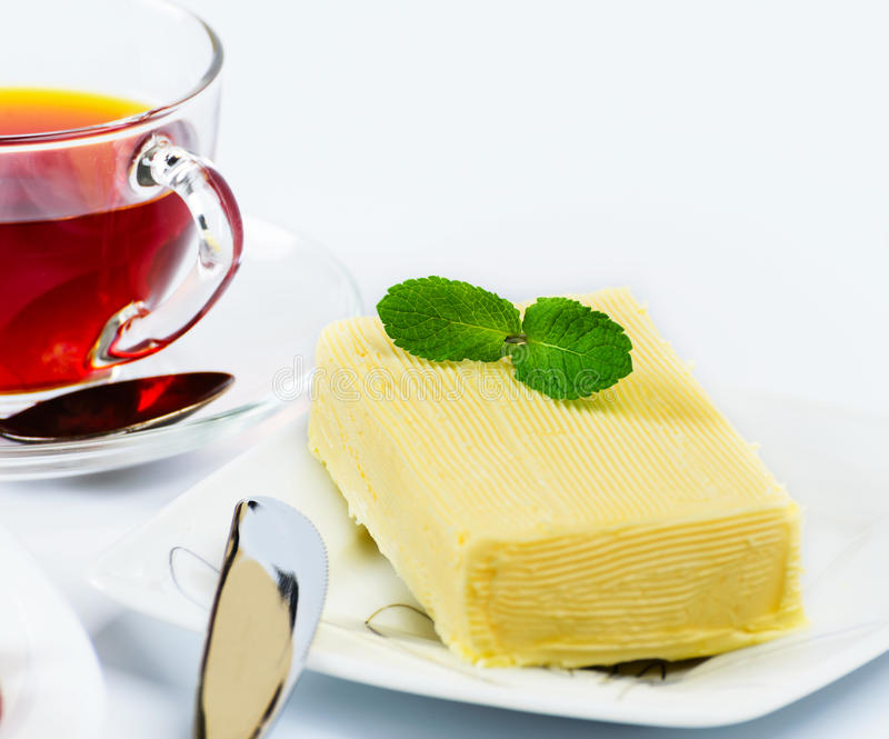 Briquette butter. With a sprig of mint stock images