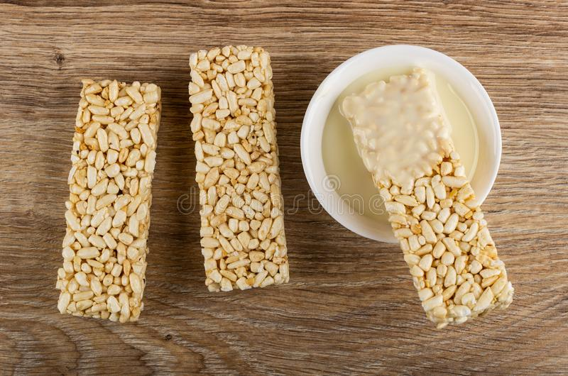 Briquette of puffed rice, puffed rice in bowl with condensed milk on table. Top view. Briquette of puffed rice, puffed rice in bowl with sweet condensed milk on stock photos