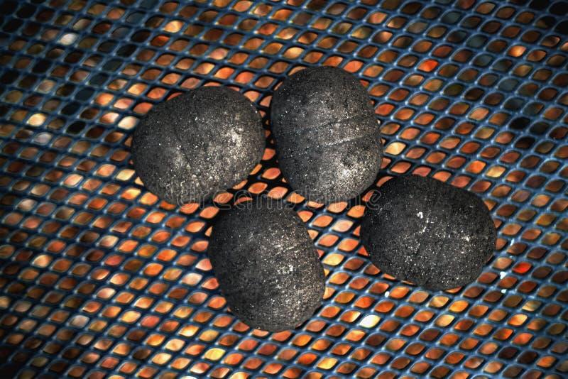 Briquettes de charbon noires sur des grils en métal images libres de droits