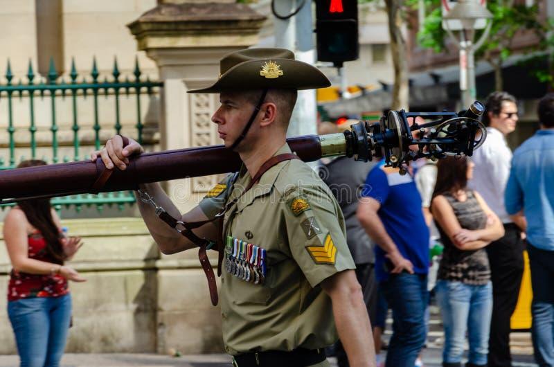 BRISBANE, AUSTRALIA - 25 DE ABRIL DE 2014: Marchas el soldado que llevan de un equipo de la encuesta sobre más allá de las muched fotografía de archivo