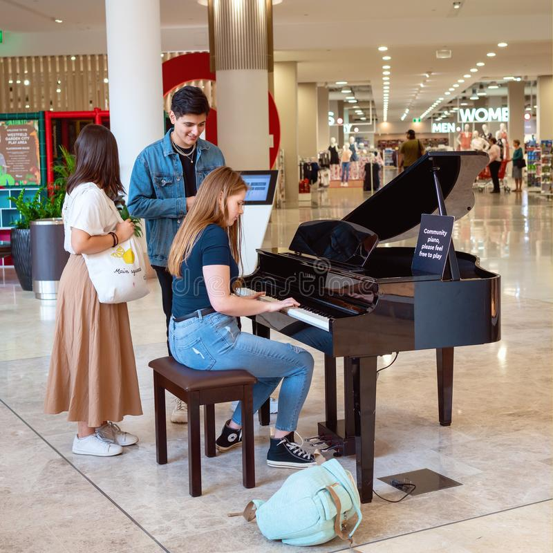 Woman Playing A Community Piano In A Shopping Mall royalty free stock image