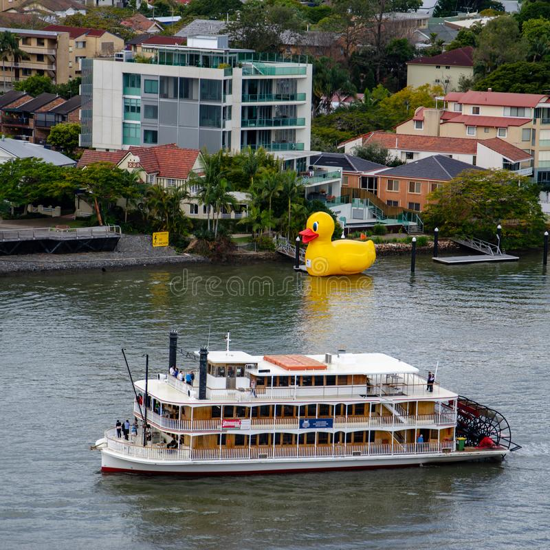 A paddle-steamer sails past a large yellow rubber duck royalty free stock images