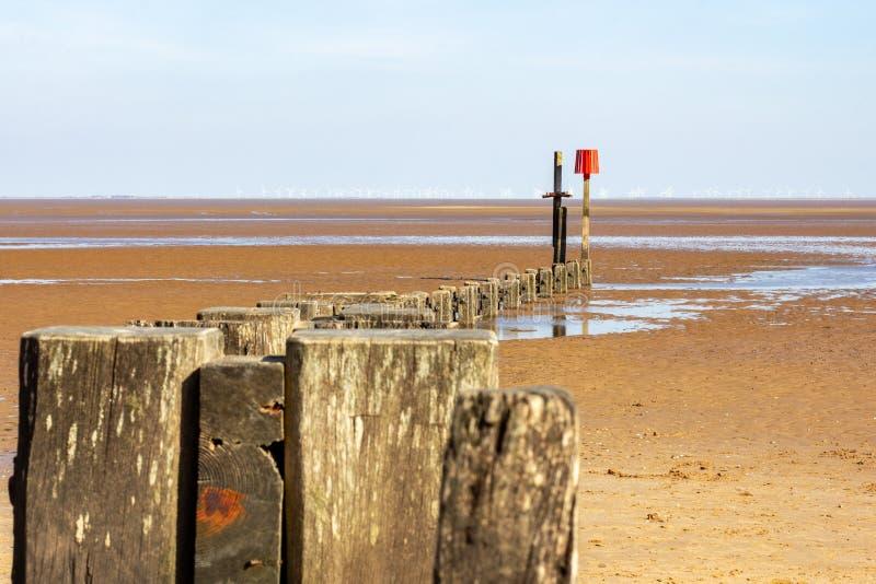 Brise-lames en bois sur la plage de Cleethorpes avec des turbines de vent dans la distance photos stock