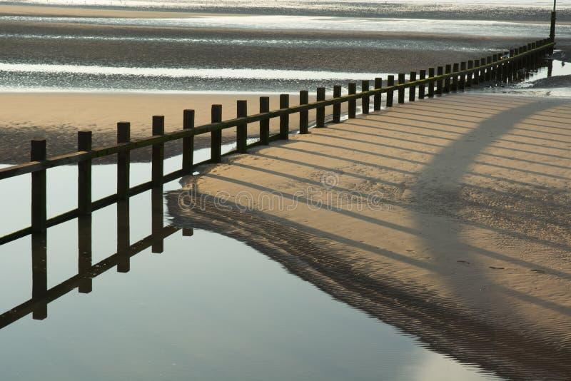 Brise-lames sur une plage sablonneuse images stock