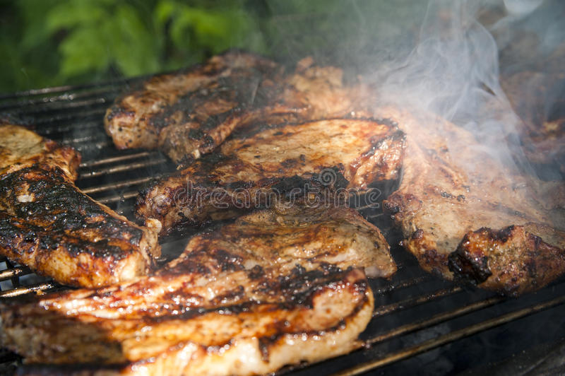 Brisket steaks on a grill. Well cooked delicious brisket steaks on a hot grill with a smoke royalty free stock image