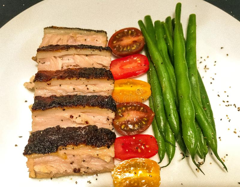 Brisket with vegetables. White china plate with slices of Texas salt and pepper brisket, cherry or grape tomato halves and green beans royalty free stock image