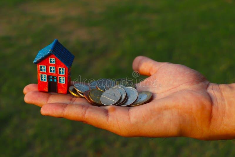 Brist av pengar som k?per ett husbegrepp Mannen rymmer leksakhuset och mynt i en hand arkivfoton