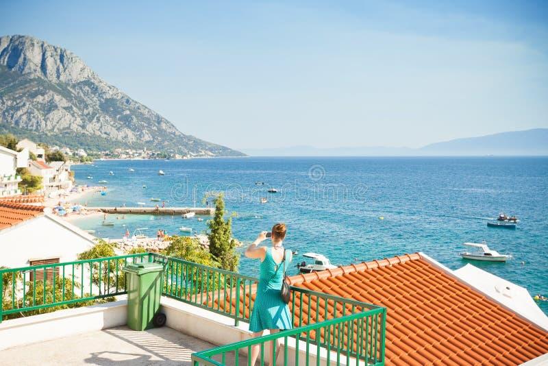 Brist, Dalmacia, Croacia - mujer que toma una imagen de la bahía hermosa de Brist imagen de archivo libre de regalías