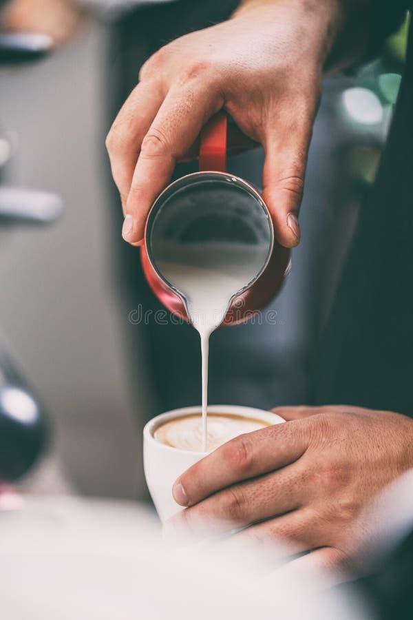 Brista que añade la leche al café imagen de archivo
